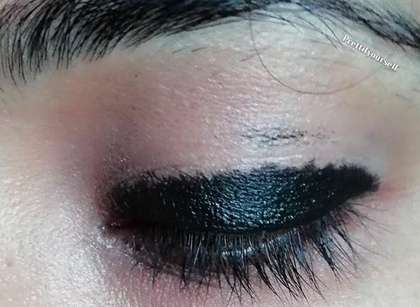 applying kajal on eye lid